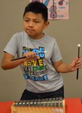 A student does a little dance while playing the glockenspiel
