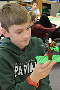 Mason Dennis creates a Lego tree for his group's claymation video