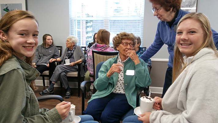 Amber Wineland, left, and Alexia Jansma savor some hot chocolate and good conversation with residents of StoryPoint senior living community