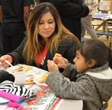 Janet Maldonado and first-grader Emily Amador eat at the Las Posadas feast