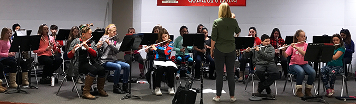An assistant from Grand Valley State University works with the Kent City woodwind section on their holiday concert music