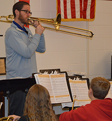 Kent City band director Jonathan Schnicke demonstrates articulation on his trombone
