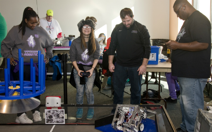 Rozalyn Zachary, left, an eighth-grader at Wyoming Junior High, looks on while classmate Jericha Skinner tries the Robotics Demo/Scrimmage. Justin VanEtten, a robotics coach from Wyoming Junior High, and Rosalyn's dad, Jason, offer moral support