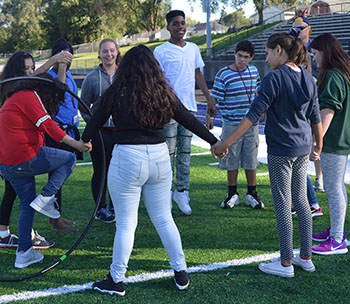 Students pass around a hula hoop during the problem-solving activity