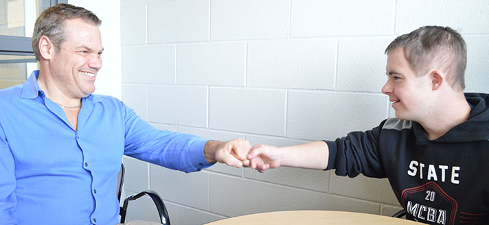 Kyle Bueche gives a fist bump to teacher Tom Mertz