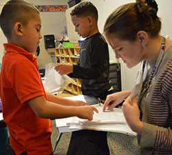 First-grader Gustavo Aburto Ambriz shows his story to EL teacher Nicole Adams