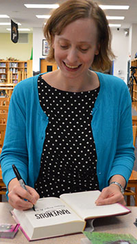 MarcyKate Connolly signs a book for the Lee Middle-High School media center