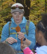 Naturalist guide Kelly Morrissey describes a beech leaf to students on the trail of Rosy Mound Natural Area
