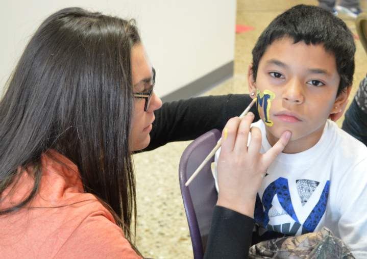 Fourth-grader Usher Laurencio gets his face painted by Hannah Kimzler, a Grandville High School sophomore