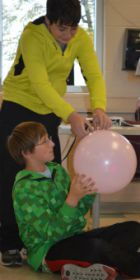 Aaron Behm, standing, helps Peyton Morgan prepare his balloon
