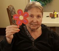 American House resident Vergie Schuitema shows off her flower craft