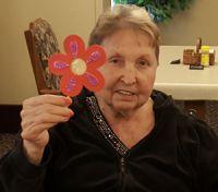 American House resident Vergie Schuitema shows off her flower craft
