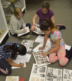 Kent City fifth-graders amid yearbooks and newspaper clippings on the historical society floor
