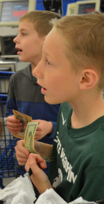 Evan Standley and Jackson Bernal watch the register totals as they hand over their group's money