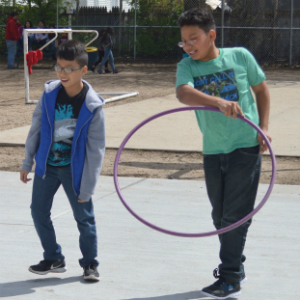 Fifth-graders Eduardo Mazariegos and Ambrosio Lemus play with hula hoops on the new concrete surface