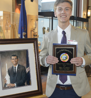 Stefan with a portrait of Roger B. Chaffee, the late astronaut for whom the scholarship is named