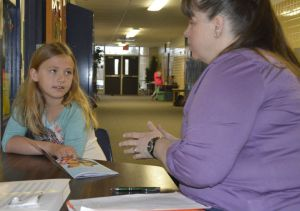 Central Elementary parent volunteer Stephanie Lapinski discusses a book with second-grader Eloise Tompkins; crowded classrooms force such tutoring into the hallway