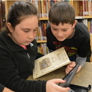 Students Micah Nagel and Taylor Walter get excited about reading a book for the camera