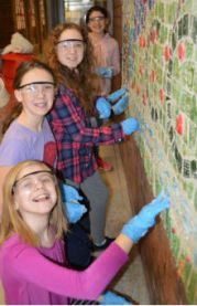 Third-graders caught smiling mid-grout are, from front to back, Joclynn Burholder, Ava Peterson, Izzy Field and Jaqlin Kraft