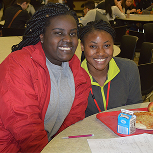 Rwandan refugee Sifa Nyamuhungu and Gloria Tungabose join each other at the lunch table