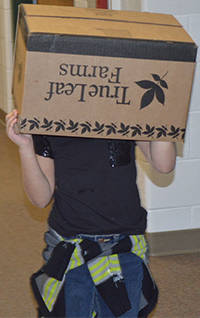 A student hides inside a cardboard box
