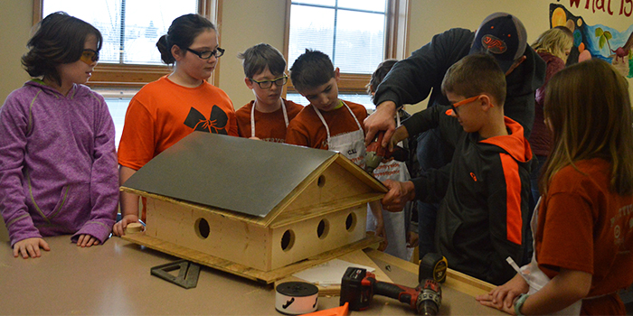 Students work on a purple martin house