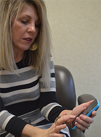 "Valerie Behm, district public relations specialist, says the new Lowell Area Schools app contains information and resources that are ""so meaningful and current, people will want to return"""