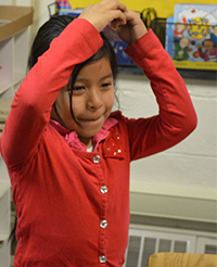 Enadina Mencho-Vail acts out flying a kite after reading about it