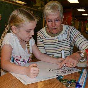 Church member Nancy Heidrich, a retired Grandville High School teacher, helps second-grader Zoey Winship with math