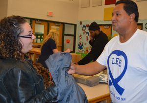 Jaime Ramirez hands a coat to a parent at the recent coat drive