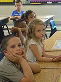 West Kelloggsviile second-grade students Natileigh Merchant and Kahari Cones make sad faces while talking about feelings with counselor Lisa VanKampen