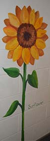 A sunflower stands tall and bright outside a preschool classroom