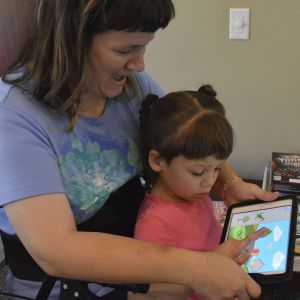 Nora Yarrington helps her daughter Cheyenne match shapes on an iPad