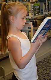 Oriole Park Elementary second-grader Ayla Wiltrout reads at the Kent District Library Wyoming branch