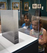 Third-graders Madileena Longoria and Kadinn Maddox view art on display