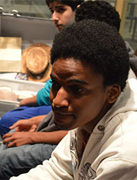 Freshman Waicel Jose Reyes sits by a suitcase packed by an immigrant in the museum's exhibit
