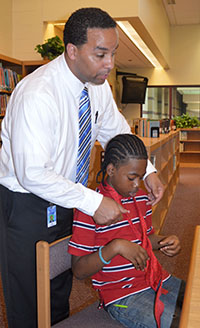 Kelloggsville Dean of Students Eric Alcorn helps sixth grader Micaus Gonzalez with his tie