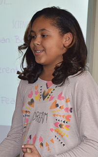 Bowen Elementary fifth-grader Mia Johnson presents a progress report about herself to her mother, Stephanie Mitchell