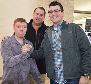 Byron Center High School senior Nick Baker, at right, greets sophomore Hunter James VandeVelde and teacher Doug Takens