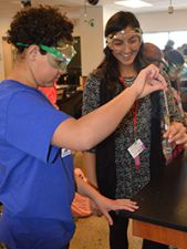Fifth-grader Samantha Harris works on a chemical reaction with sophomore Maxine Osorio in Accelerated Chemistry class