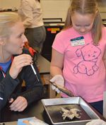 Senior Paige VanderWall shows fifth-grader Vivian Kolkman a frog and fish dissection