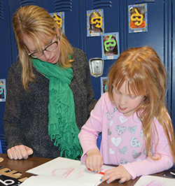 Syndey O'Keefe, 4, works with her mother, Nicole O'Keefe