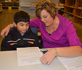 Third-grade student Daniel Rangel-Zavala works with tutor Joy Howard, who also is a paraprofessional for Kelloggsville Public Schools