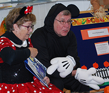Susan Bodenner and her husband, Jim, read to students as Mickey and Minnie