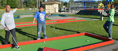 Fifth-graders Quanta Barnes, Zion Vazquez and Chris Matthews celebrated a successful putt