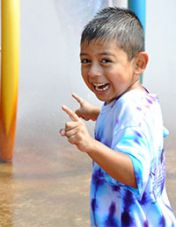 A T.E.A.M 21 student cools off the Splash Pad at Lamar Park during summer programming