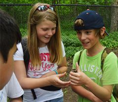 Fifth-grade students Roman Gendron and Cienna Coats check out a walnut found at the park