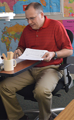 Third-grade teacher Mark Pullen grades the tests at the Checking Party