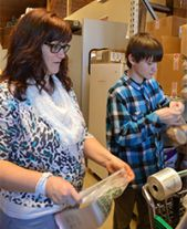 Teacher Kellie Phillips and eighth-grade student Gregory Brink get bags ready for produce