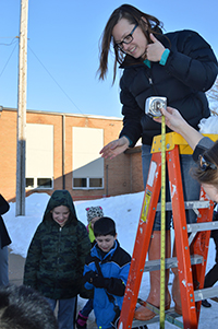 Teacher Sarah Baker looks to see if an egg has remained intact after dropping it six feet